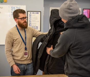 Caseworker provides winter coat to client